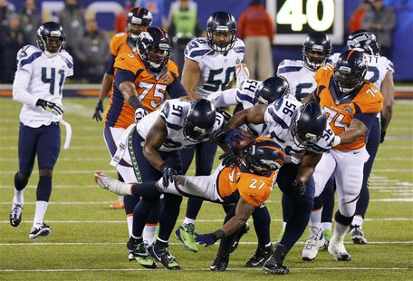 Denver Broncos Knowshon Moreno (C) is tackled by Seattle Seahawks Chris Clemons (91) in the first quarter during the NFL Super Bowl XLVIII f