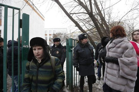 Interior Ministry members evacuate people after an armed student took hostages at a high school on the outskirts of Moscow, February 3, 2014
