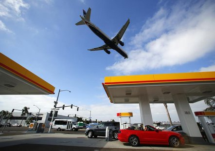 Consumers purchase gasoline at a gas station as a plane approaches to land at the airport in San Diego, California October 8, 2012. REUTERS/