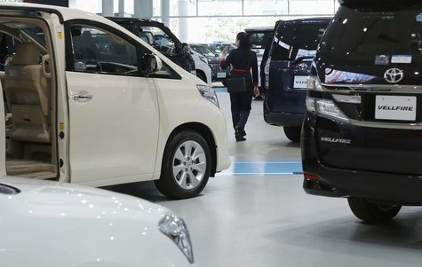 A woman walks among Toyota Motor's cars at the company's showroom in Tokyo November 6, 2013. REUTERS/Toru Hanai