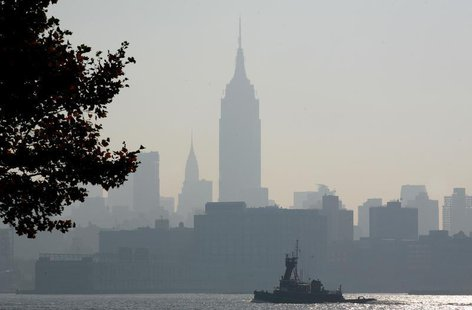 The haze shrouded skyline of New York is a backdrop for a boat moving up the Hudson River in Hoboken, New Jersey August 3, 2006. REUTERS/Gar