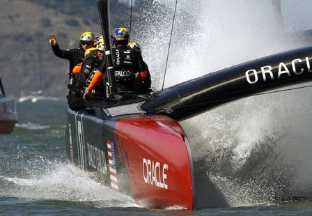 Oracle Team USA skipper Jimmy Spithill (L) waves to the crowd after defeating Emirates Team New Zealand during Race 16 of the 34th America's