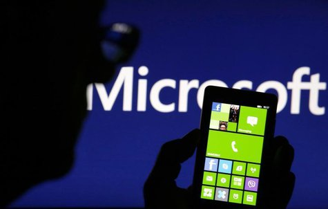 A man is silhouetted against a video screen with the Microsoft logo in the background as he poses with a Nokia Lumia 820 smartphone in this