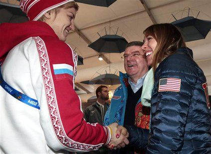 International Olympic Committee (IOC) President Thomas Bach smiles as Russia's ice hockey player Iya Gavrilova (L) and U.S speed skater Anna