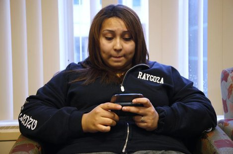 Jazmine Raygoza sends a text message to her brother and sister as she waits at Rose Medical Center in Denver June 20, 2011 just before her L