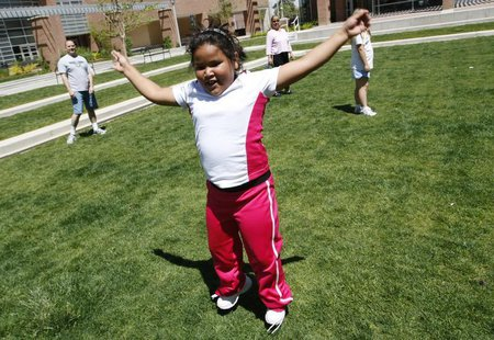 Fernanda Garcia-Villanueva, 8, does jumping jacks at a group exercise session in the 10-week Shapedown Program at The Children's Hospital in