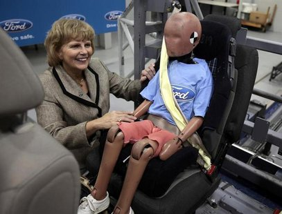 Ford Motor Vice President, Sustainability, Environment and Safety Engineering Sue Cischke shows off a child crash test dummy strapped in a S