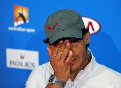 Rafael Nadal of Spain wipes his face at a news conference after losing his men's singles final match against Stanislas Wawrinka of Switzerla