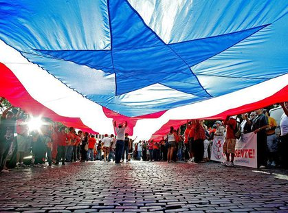 People march under a huge Puerto Rican flag in Old San Juan, Puerto Rico, October 8, 2006. REUTERS/Ana Martinez