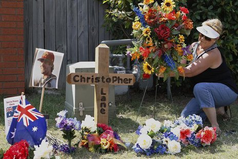 Neighborhood resident Sherrie Shannon of Duncan, Oklahoma, places flowers at a memorial at the scene where Australian college student Christ