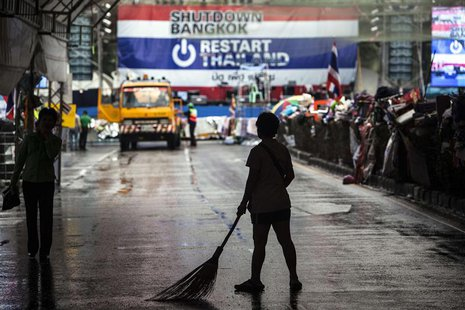 An anti-government protester cleans a street where fellow protesters are camping on a much lower scale after Sunday's general election, in B