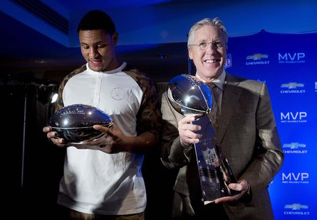Seattle Seahawks linebacker and Malcolm Smith (L) looks at his Most Valuable Player trophy as head coach Pete Carroll holds the Vince Lombar