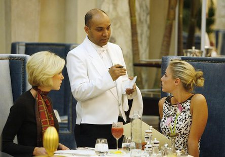 "Waiter Sayed Islam (C) speaks with Kelley Ruland (R) and Brittany Parker in ""The Plaza"" hotel's ""Palm Court"" the first day that the hotel re"