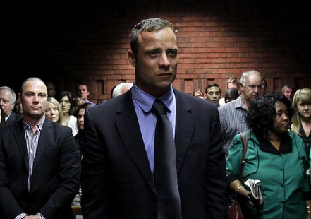 Oscar Pistorius awaits the start of court proceedings while his brother Carl (L) looks on, in the Pretoria Magistrates court February 19, 20