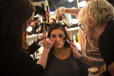 A model has make up applied before the GS Shop Lingerie Show featuring Wonderbra, Anna Sui and Spanx Fall 2014 collections during New York F