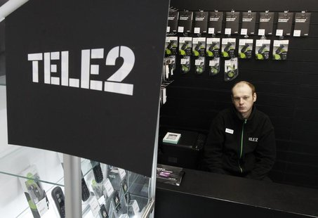 A shop assistant looks on from inside a Tele2 company's sales office in St. Petersburg, March 28, 2013. REUTERS/Alexander Demianchuk