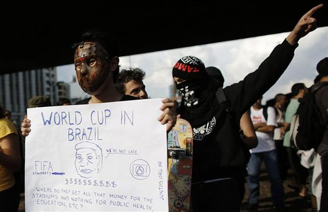 A man wearing a mask holds a banner during a protest against the 2014 World Cup, in Sao Paulo January 25, 2014. REUTERS/Nacho Doce