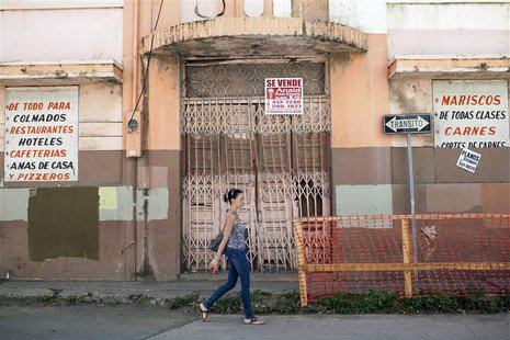 A woman walks past a closed restaurant in Ponce, on Puerto Rico's southern coast, February 5, 2014. REUTERS/Alvin Baez