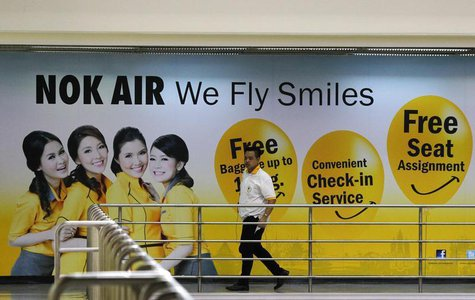 A Nok Air staff member walks past a commercial for the airlines at Don Muang International Airport in Bangkok June 20, 2013. REUTERS/Chaiwat