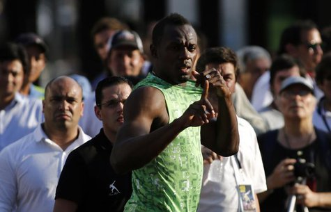 Jamaican sprinter Usain Bolt gestures before competing in a race against a public bus during a demonstration event in Buenos Aires December