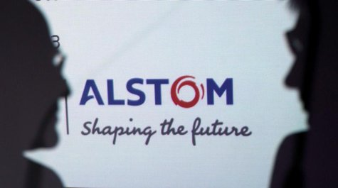 People are silhouetted in front on an Alstom logo during a news conference to present the group's first half results at the company headquar