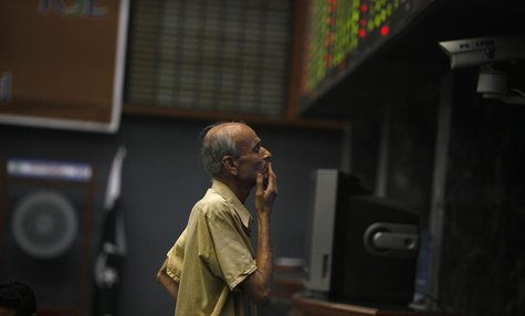A man reacts as he monitors share prices during a trading session at the Karachi Stock Exchange May 21, 2013. REUTERS/Akhtar Soomro