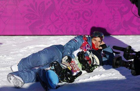 Russia's Alexey Sobolev poses lying in the snow at the finish line during the men's slopestyle snowboarding qualifying session at the 2014 S