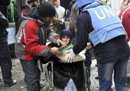 Residents receive food aid distributed by the U.N. Relief and Works Agency (UNRWA) at the besieged al-Yarmouk camp, south of Damascus Februa