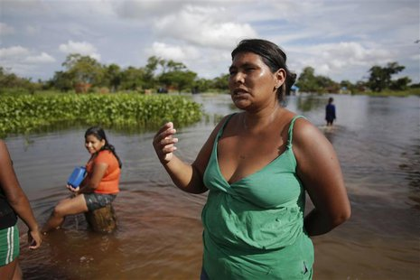 A woman speaks along a flooded street on the outskirts of Trinidad, some 400 km (249 miles) northeast of La Paz February 5, 2014. REUTERS/Da