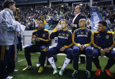Los Angeles Galaxy midfielder Robbie Rogers (14) sits on his team bench in front of head coach Bruce Arena before their MLS soccer game agai