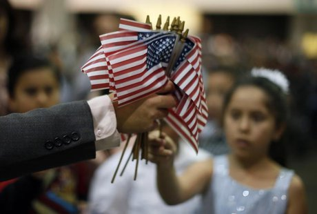 A man hands out U.S. flags at a naturalization ceremony for 3,703 new U.S. citizens from 130 countries, in Los Angeles, California, December
