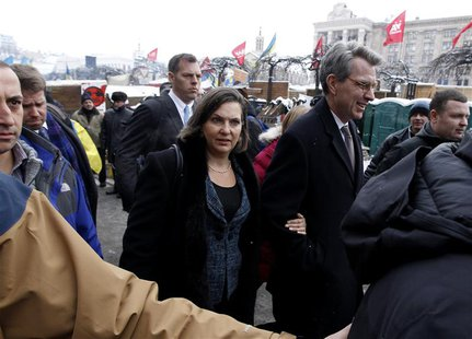 U.S. Assistant Secretary of State for European and Eurasian Affairs Victoria Nuland (C) and U.S. Ambassador Geoffrey Pyatt walk in the oppos