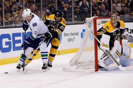 Feb 4, 2014; Boston, MA, USA; Vancouver Canucks center Henrik Sedin (33) battles with Boston Bruins defenseman Zdeno Chara (33) behind the n