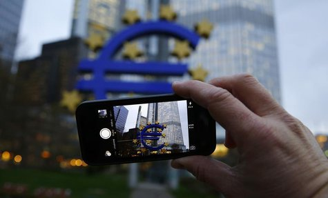 A man uses his mobile phone to take a picture of the euro sculpture outside the head quarters of the European Central Bank (ECB) in Frankfur
