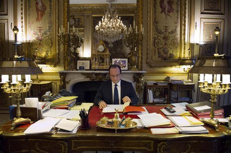 French President Francois Hollande works in his office during a photo session at the Elysee Palace in Paris, in this December 17, 2012 file