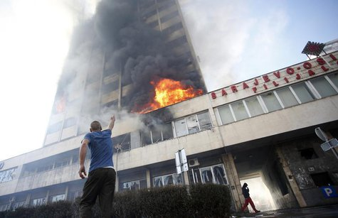 A man points as people attempt to put out a blaze at a government building in Tuzla February 7, 2014. REUTERS/Dado Ruvic