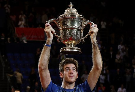 Juan Martin Del Potro of Argentina raises the winner's trophy after he won his final match against Switzerland's Roger Federer at the Swiss