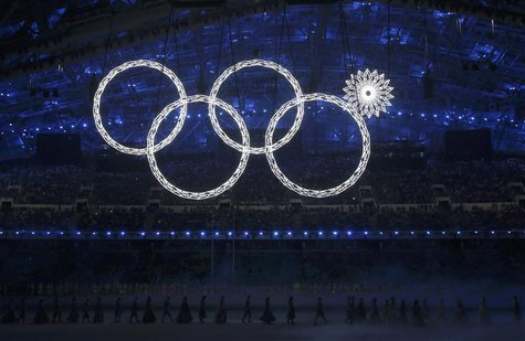 Participants march by as one of the Olympic Rings fails to completely illuminate during the opening ceremony of the 2014 Sochi Winter Olympi