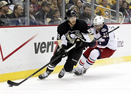 Dec 9, 2013; Pittsburgh, PA, USA; Pittsburgh Penguins defenseman Kris Letang (58) handles the puck against pressure from Columbus Blue Jacke