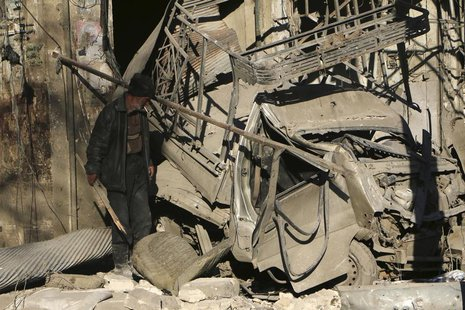 A man looks at a damaged pick-up truck at a site hit by what activists said was shelling by forces loyal to Syria's President Bashar al-Assa