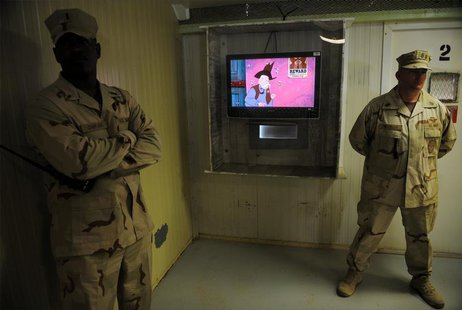 Guards stand next to a television showing a cartoon as journalists visit the movie room at the Camp Four detention facility at the U.S. Nava
