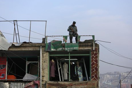 An Afghan policeman stands guard on the roof of a shop damaged in a suicide attack in Kabul January 26, 2014. REUTERS/Mohammad Ismail