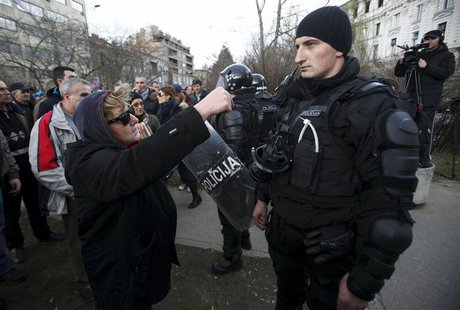A protester speaks to a police officer in front of a government building in Sarajevo February 8, 2014. REUTERS/Antonio Bronic