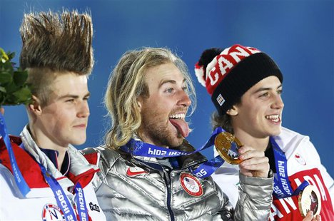 Gold medalist Sage Kotsenburg of the U.S., silver medalist Staale Sandbech (L) of Norway and bronze medalist Mark McMorris (R) of Canada rea