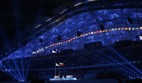The Olympic flag and Russian national flag (C) are raised during the opening ceremony of the 2014 Sochi Winter Olympics, February 7, 2014.  CREDIT: REUTERS/JIM YOUNG