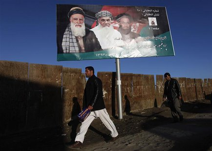 Men walk past a campaign banner of Afghan presidential candidate Abdul Rassoul Sayyaf, in Kabul February 9, 2014.REUTERS/Mohammad Ismail