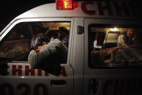 A relative (L) mourns his family member, who was killed by unknown gunmen, next to his body in an ambulance, outside the Civil Hospital morg