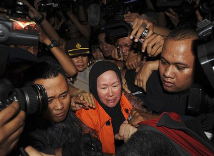 Banten governor Ratu Atut Chosiyah (C), wearing an KPK orange vest, walks as she is detained at the national anti-graft agency (KPK) office