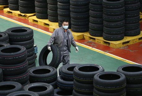 An employee carries a tyre at a tyre factory in Jiaxing, Zhejiang Province, January 27, 2014. REUTERS/William Hong