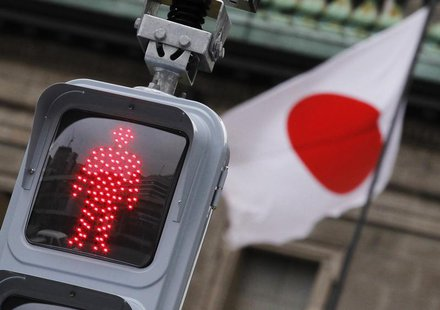 "A ""Don't Walk"" traffic signal is seen in front of the national flag hoisted on the headquarters of Bank of Japan in Tokyo February 8, 2012."